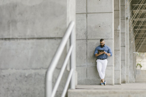 Bearded hipster businessman leaning against concrete wall using tablet - FMGF00019