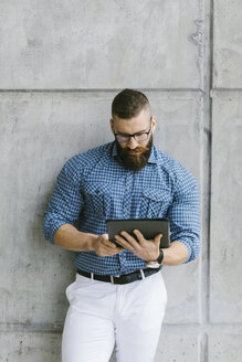 Bearded hipster businessman wearing glasses and plaid shirt leaning against wall using tablet - FMGF00022
