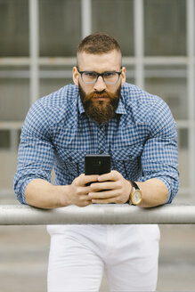 Portrait of bearded hipster businessman with smartphone  leaning on railing - FMGF00025
