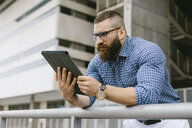 Bearded hipster businessman wearing glasses, wrist watch and plaid shirt using digital tablet - FMGF00028