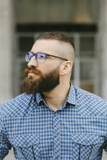 Portrait of bearded hipster businessman wearing glasses and plaid shirt - FMGF00031
