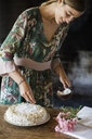 Smiling young woman garnishing home-baked cake - ALBF00605