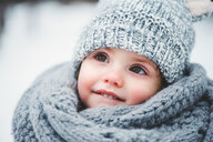 Close up portrait of a cute baby girl wearing warm clothing in the snow - INGF00024