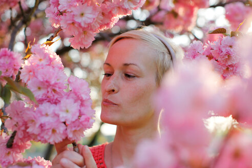 Close-up portrait of a woman posing with pink flowers in bloom - INGF00117