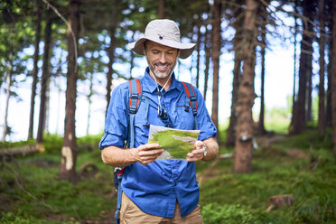 Smiling man looking at map during a hike in the forest - BSZF00661
