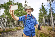 Man taking a selfie with his cell phone during hiking trip - BSZF00667