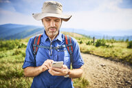 Man checking his cell phone during hiking trip - BSZF00670