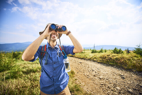Man looking through binoculars during hiking trip - BSZF00673