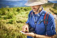 Man checking his cell phone during hiking trip - BSZF00676