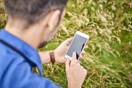 Close-up of man checking his cell phone during hiking trip - BSZF00682