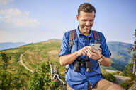 Smiling man checking his cell phone during hiking trip - BSZF00718