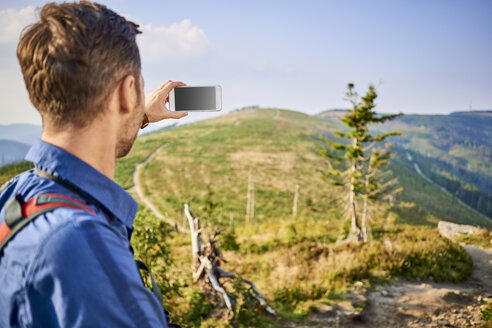 Man taking picture with his cell phone during hiking trip in the mountains - BSZF00721