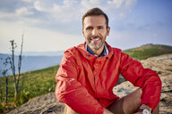 Portrait of smiling man sitting on rock during hiking trip - BSZF00724