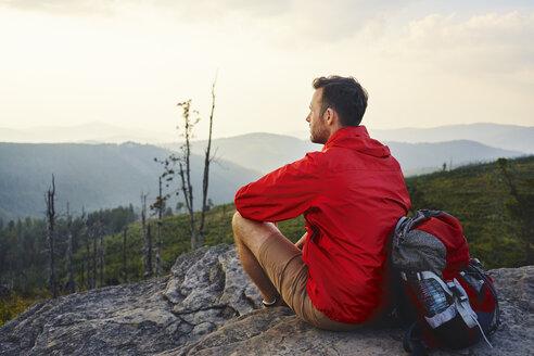 Man sitting on rock enjoying the view during hiking trip - BSZF00730