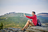 Man sitting on rock taking selfie with his cell phone during hiking trip in the mountains - BSZF00733