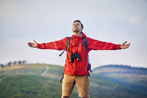 Man standing with outstretched arms on mountain top - BSZF00736