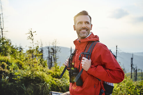 Portrait of smiling man hiking in the mountains - BSZF00739