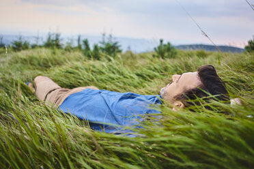 Relaxed man lying in grass - BSZF00748