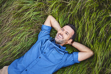 Relaxed happy man lying in grass - BSZF00751