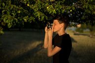 A young photographer with a retro film photo camera in the garden - INGF00139