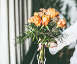 Close-up of a hand holding fresh flowers - INGF00157