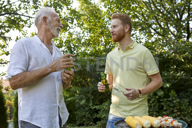 Senior father and adult son having a barbecue and talking in garden - ZEDF01581