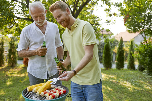 Senior father and adult son having a barbecue in garden - ZEDF01584
