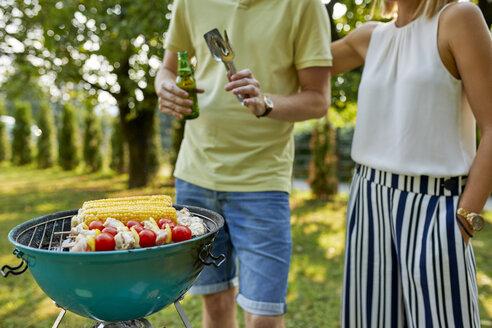 Young couple having a barbecue in garden - ZEDF01587