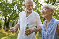 Happy senior couple having a barbecue in garden - ZEDF01596