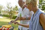 Senior couple having a barbecue in garden - ZEDF01599