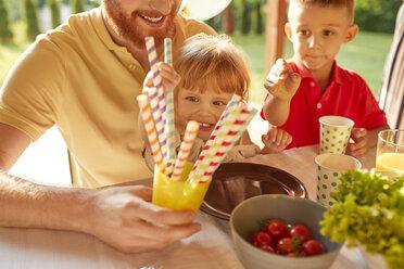 Children taking straws a garden party - ZEDF01617