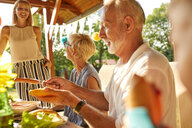 Senior man preparing a hot dog on a garden party - ZEDF01623