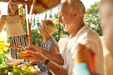Senior man preparing a hot dog on a garden party - ZEDF01623