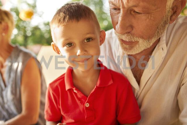 Portrait of smiling boy on grandfather's lap - ZEDF01629