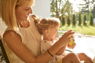 Happy mother and daughter blowing soap bubbles on porch - ZEDF01632