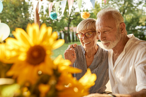 Happy senior couple embracing on a garden party - ZEDF01638