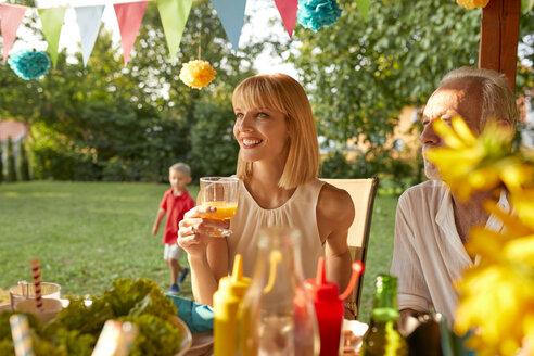 Smiling woman drinking orange juice on a garden party - ZEDF01641