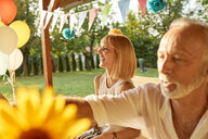 Happy woman and senior man on a garden party - ZEDF01644