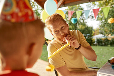 Playful father with son on a garden birthday party - ZEDF01650