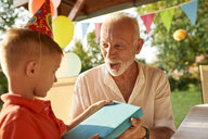 Grandfather handing over present to grandson on a garden birthday party - ZEDF01653
