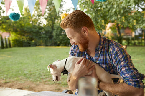 Happy man with dog on a garden party - ZEDF01656