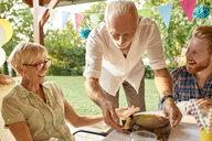 Senior man serving cake on a garden party - ZEDF01659