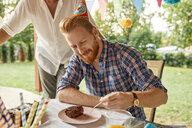 Man eating cake on a birthday garden party - ZEDF01677
