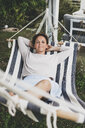 Portrait of smiling woman lying in a hammock - HMEF00019