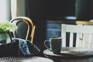 A steaming coffee mug on a table at home - INGF00293