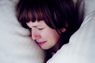 Head shot of a young woman crying in her bed - INGF00302