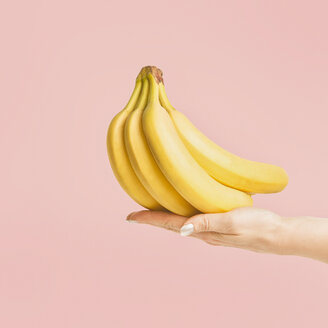 Close-up of a human hand holding a banana - INGF00338