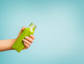 A woman holding a green drink against a blue background - INGF00344