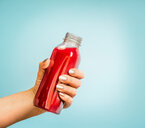 A human hand holding a rec bottle against a blue background - INGF00347