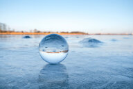 Close-up nature shot of a crystal ball on the ice during winter - INGF00443